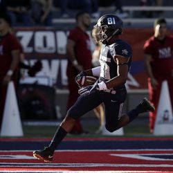 Utah State wide receiver Savon Scarver scores a touchdown on a kickoff against New Mexico State in the first half of the Arizona Bowl NCAA college football game Friday, Dec. 29, 2017, in Tucson, Ariz. (AP Photo/Rick Scuteri)