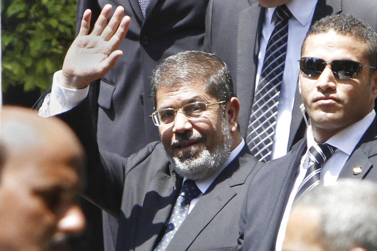 Egyptian President Mohammed Morsi waves as he leaves the Arab League headquarters.