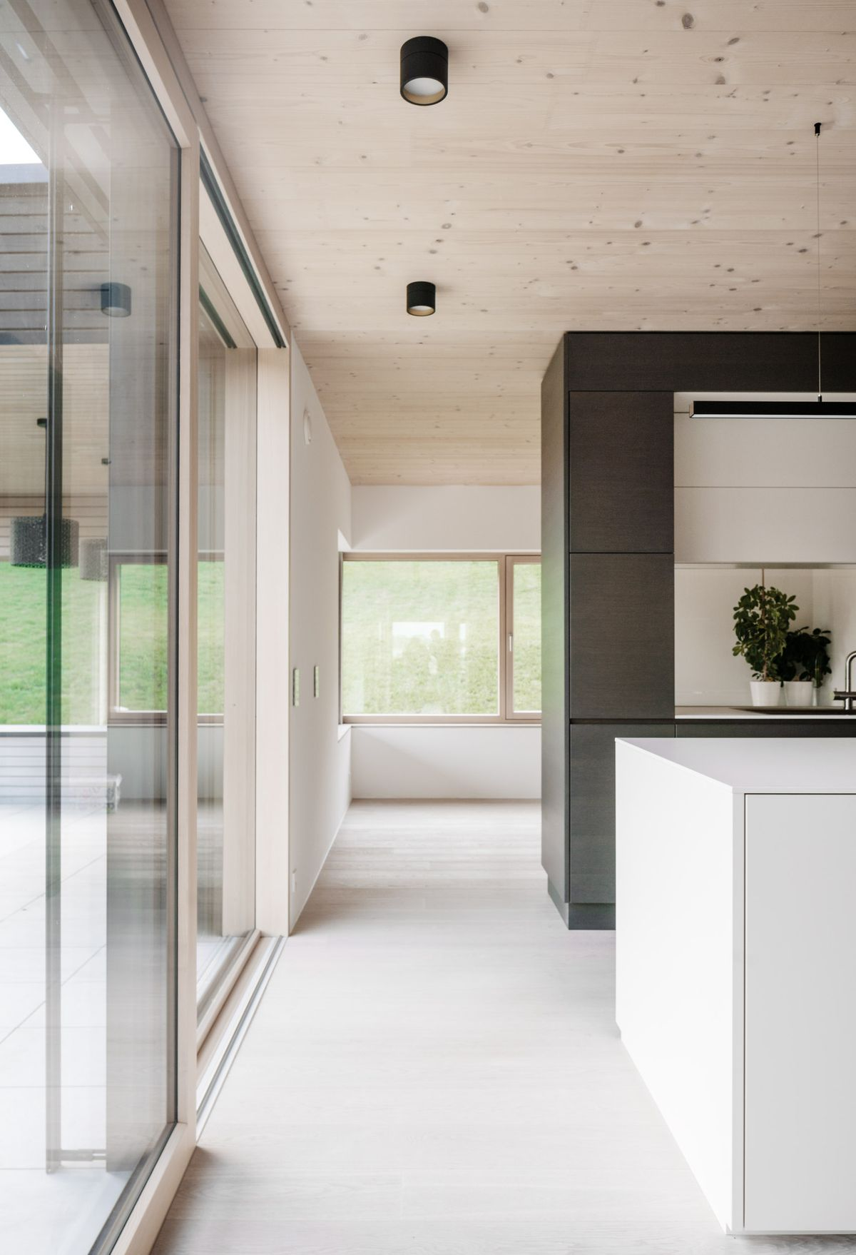 Hallway in brightly lit home with sliding glass walls.