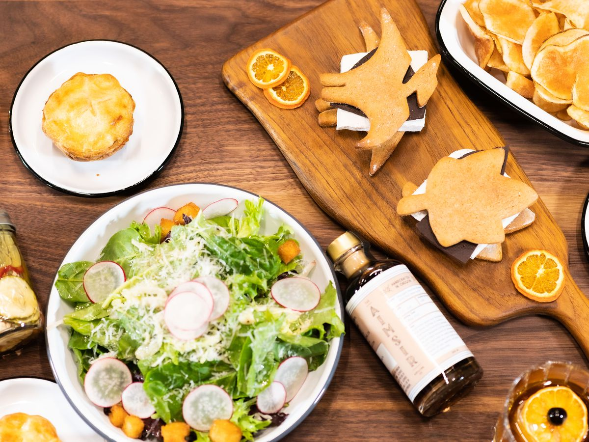 A wooden table is laden with a large bowl of salad, a bottled bourbon drink, a single hand pie on a white plate, and a wooden paddle topped with a leaf-shaped and a pterodactyl-shaped s'more.