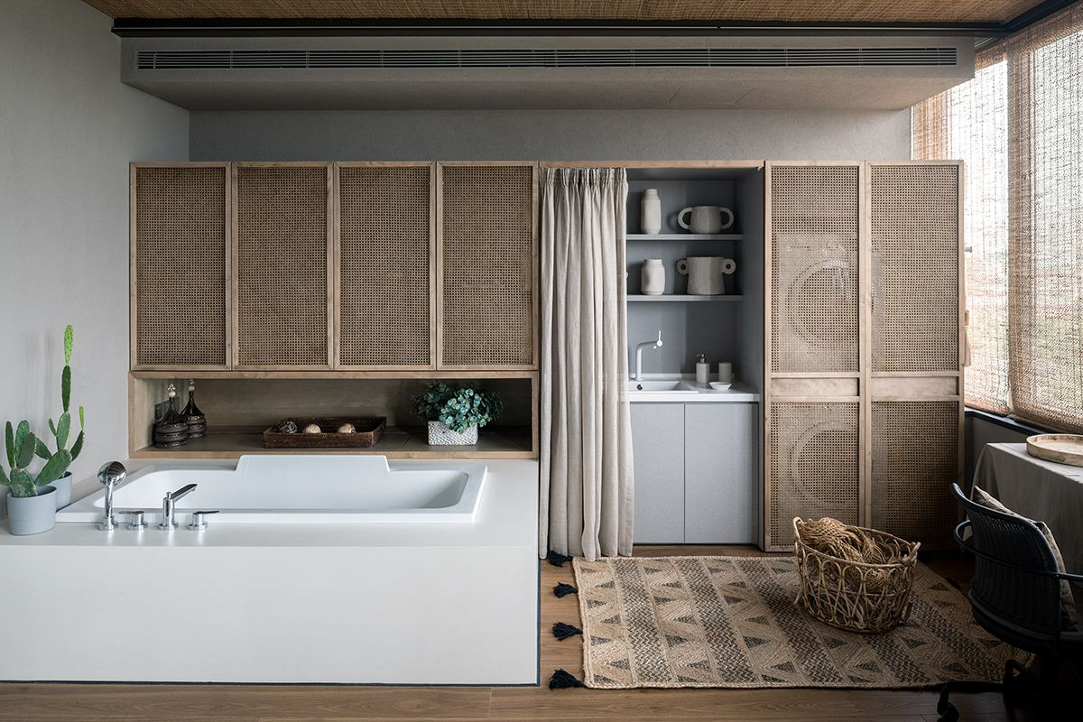 In the laundry room, storage and machines are hidden behind rattan screens. A sink is in the foreground.