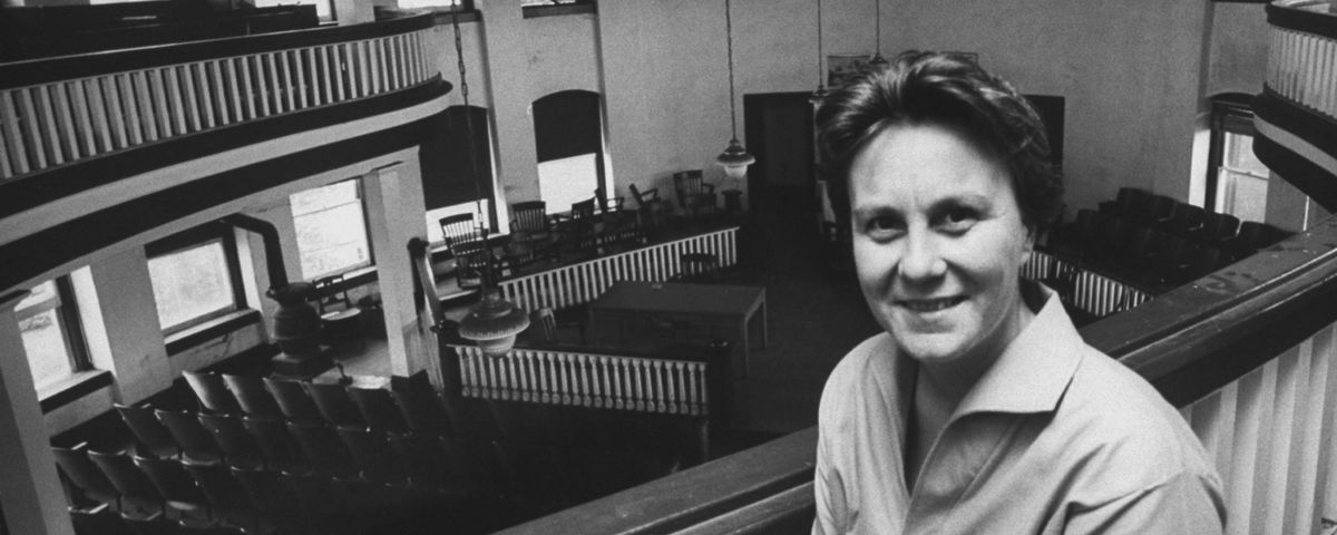 Harper Lee sitting in an upper balcony of a court house.
