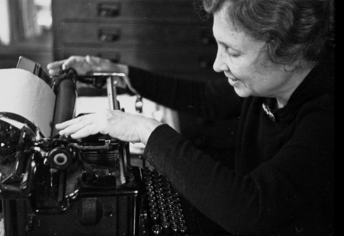 Black and white photo of Helen Keller sitting at a typewriter.