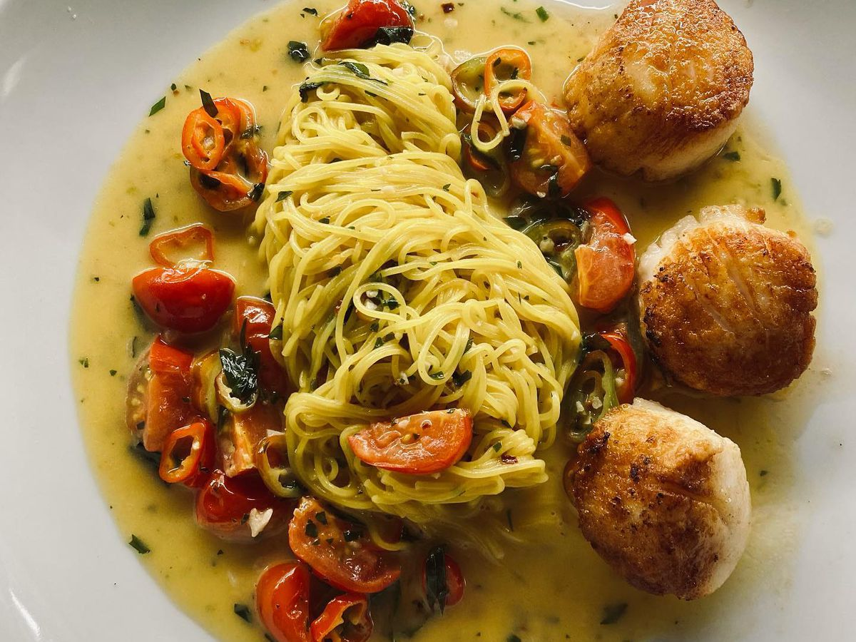 A plate with broth, a pile of capellini pasta and halved cherry tomatoes and seared scallops