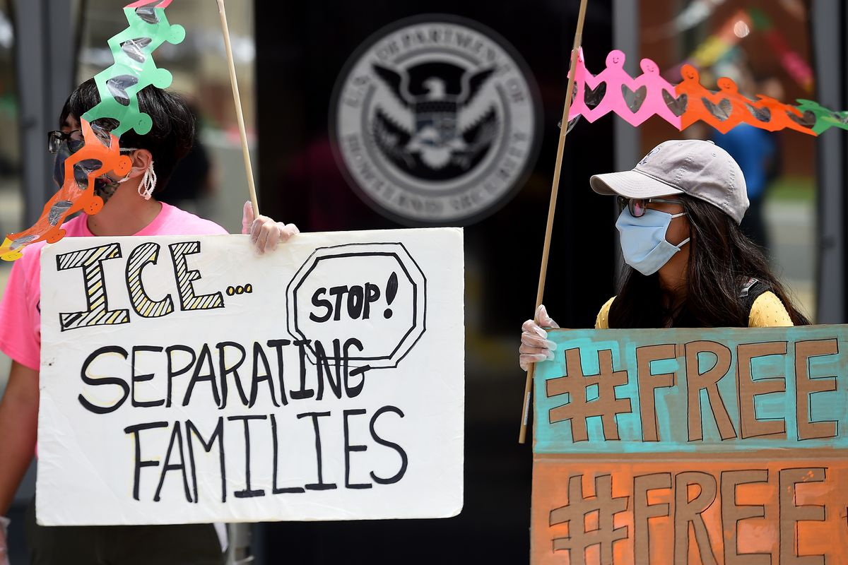 """Protesters carry signs that read, """"#Free"""" and """"ICE - Stop separating families!"""""""