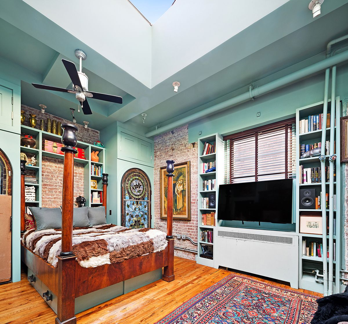 A bedroom with a small bed, exposed brick, and blue shelves surrounding it.
