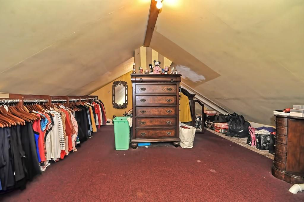 An attic with a peaked roof, a dresser in the middle, and a row of clothes down one side.