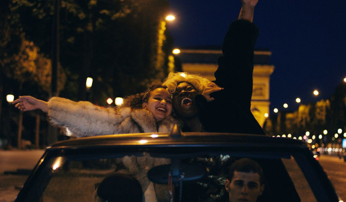 Divines: two young girls stand out a car window and shout with the arc de triomphe in the background