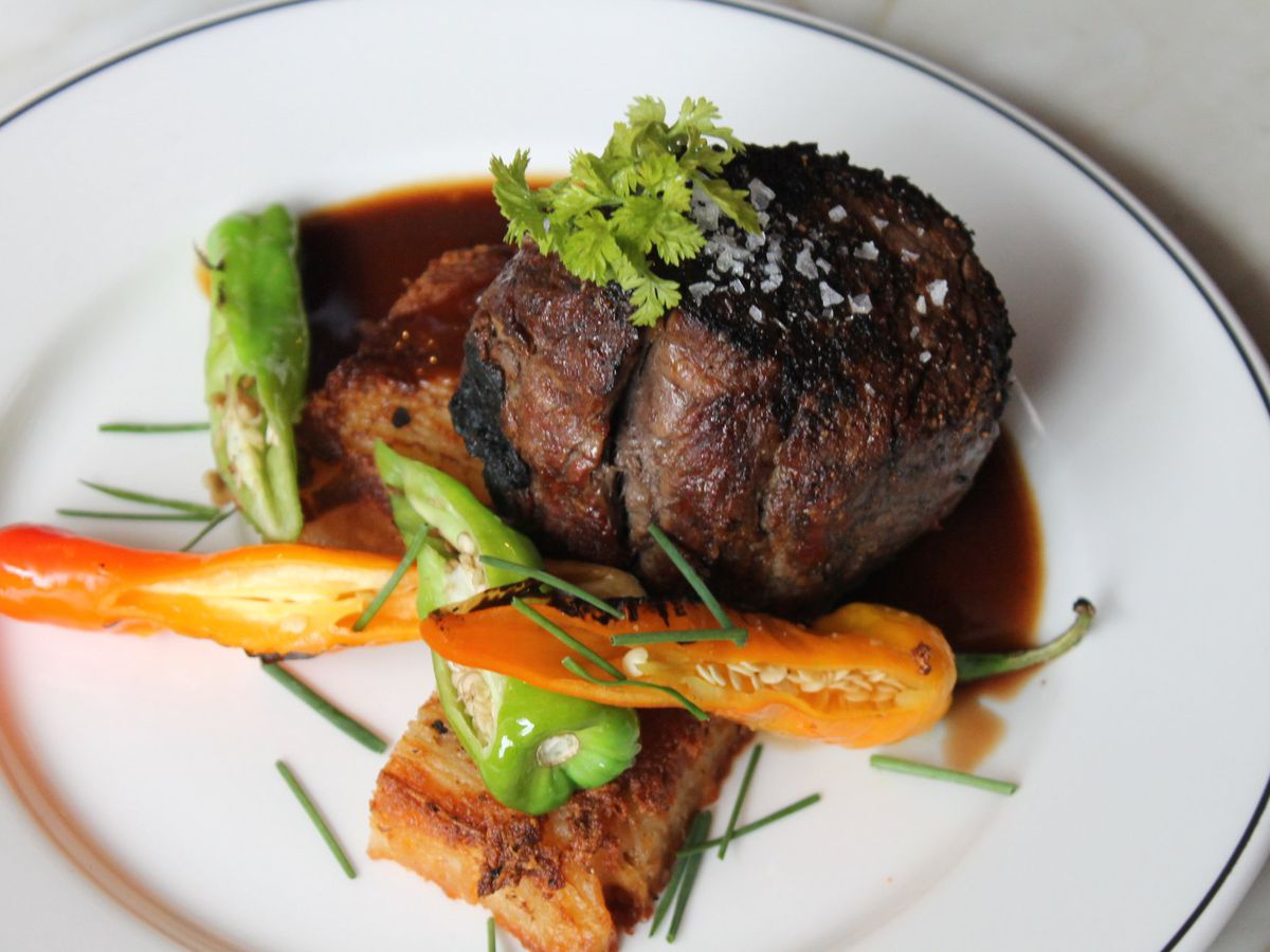 14 oz Bone-in Filet with potato pave, roasted shishito peppers and peach bordelaise on a white plate