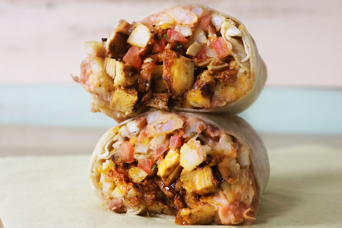 Two halves of a chicken burrito rest on a counter, overflowing with chunks of meat, refried beans, french fries, and cheese