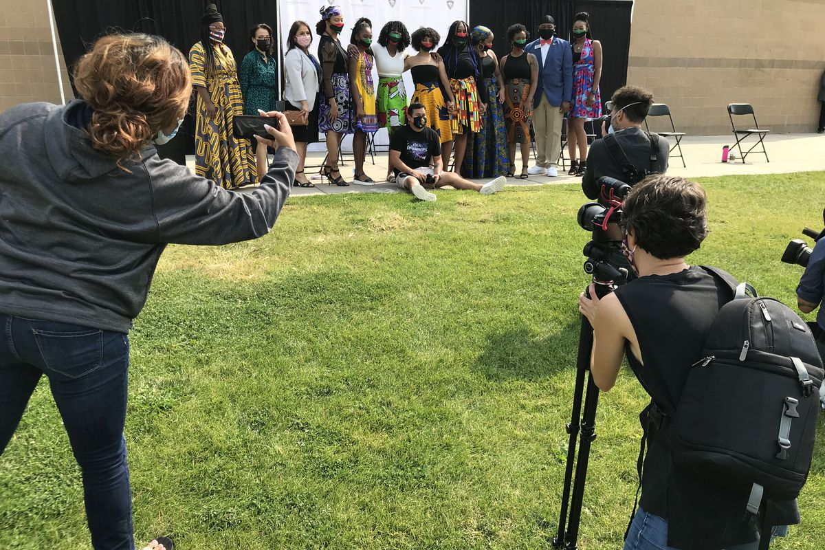 Students smile while media takes photos.
