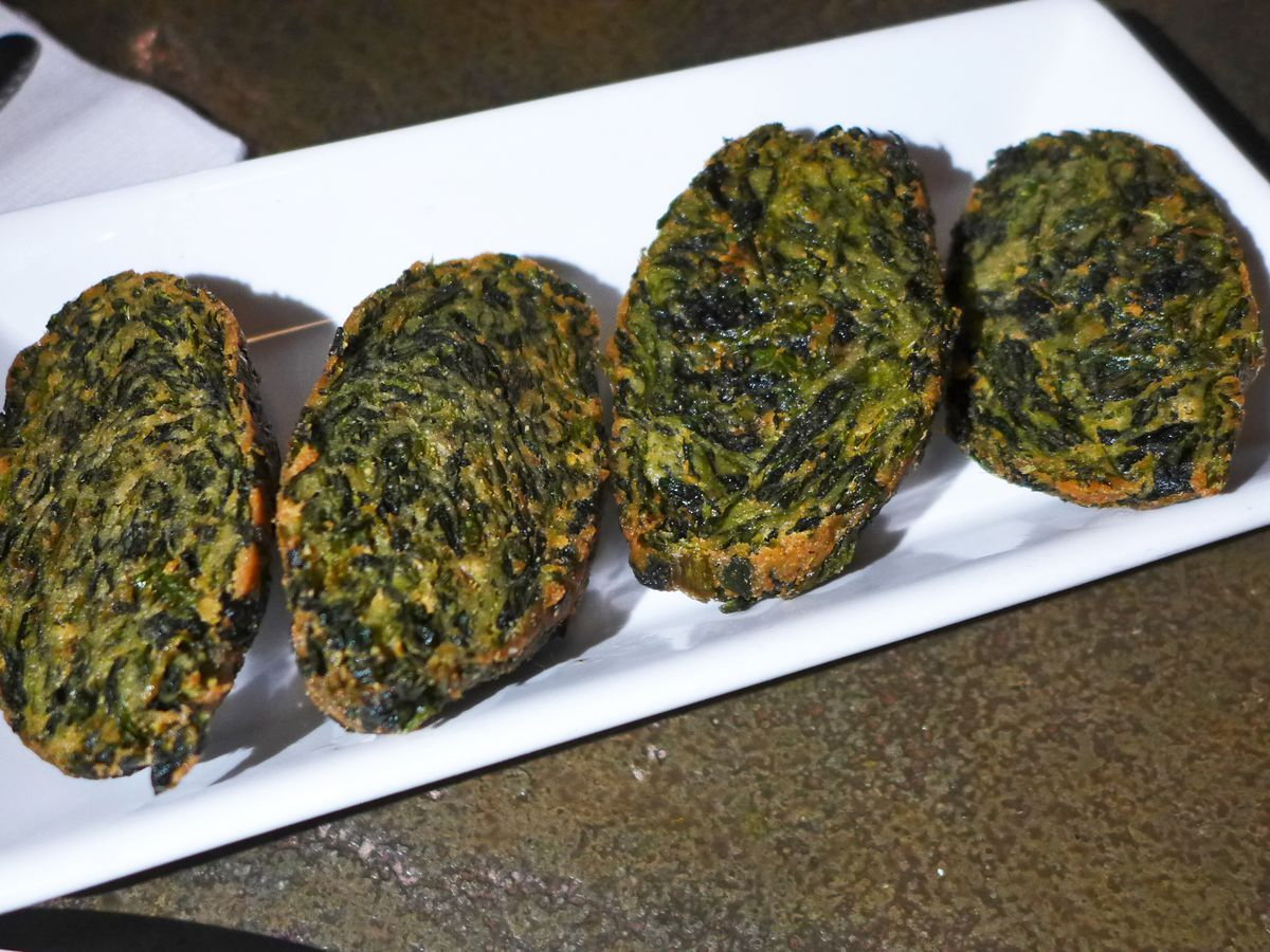 Four spinach fritters on a white plate