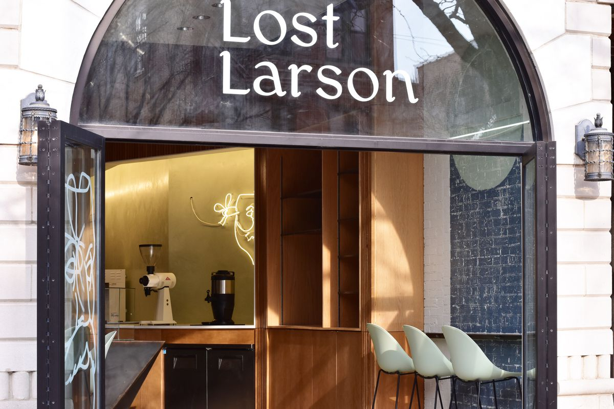 """An arc-shaped entry to a cafe. It reads """"Lost Larson"""" in white letters above the door."""