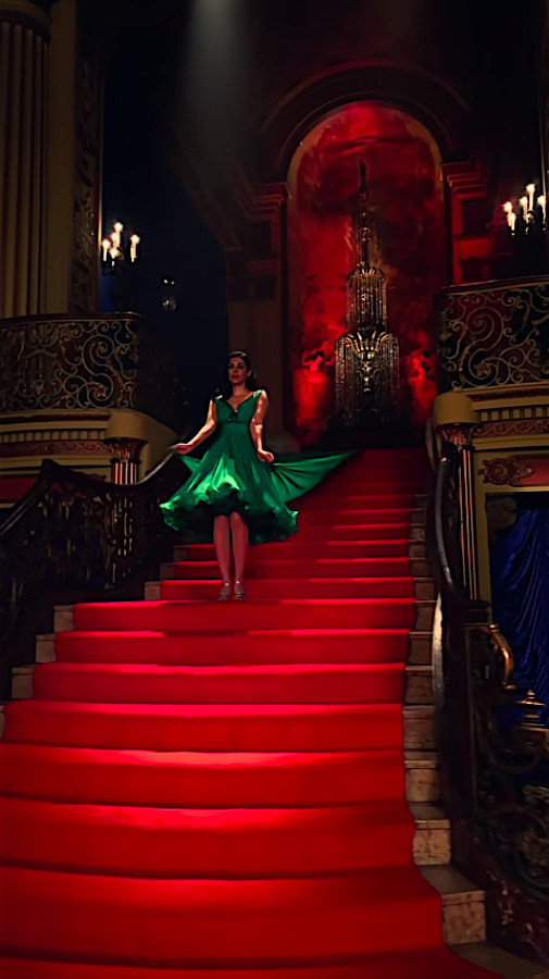"""A woman in a bright green dress stands on a bright red staircase in """"Vertical Cinema"""""""