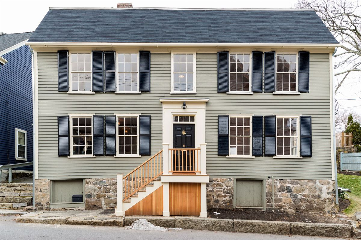 Colonial home with wood-siding and shuttered windows.