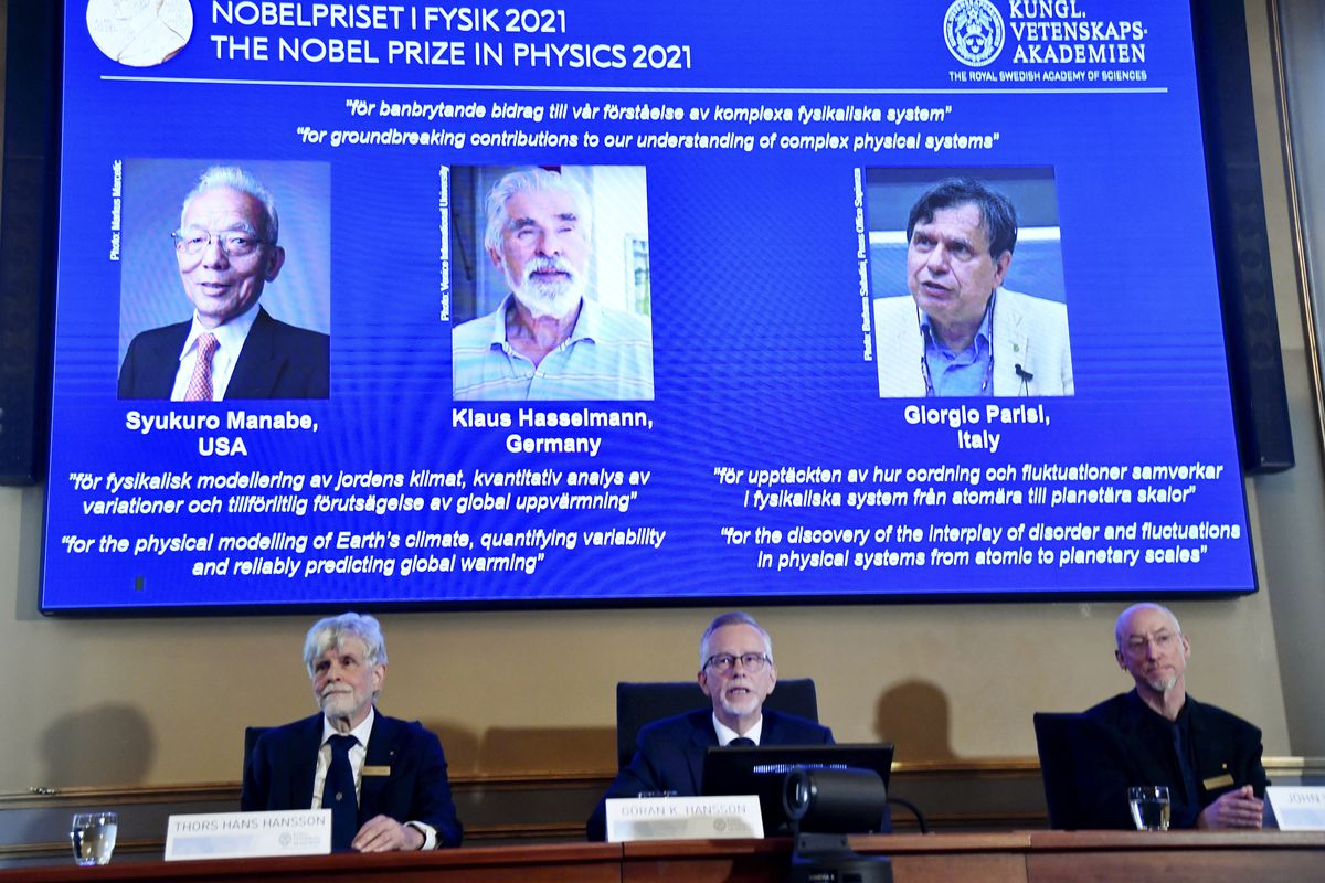 Secretary General of the Royal Swedish Academy of Sciences Goran Hansson, center, flanked at left by member of the Nobel Committee for Physics Thors Hans Hansson, left, and member of the Nobel Committee for Physics John Wettlaufer, right, announces the winners of the 2021 Nobel Prize in Physics at the Royal Swedish Academy of Sciences, in Stockholm, Sweden, Tuesday, Oct. 5, 2021.