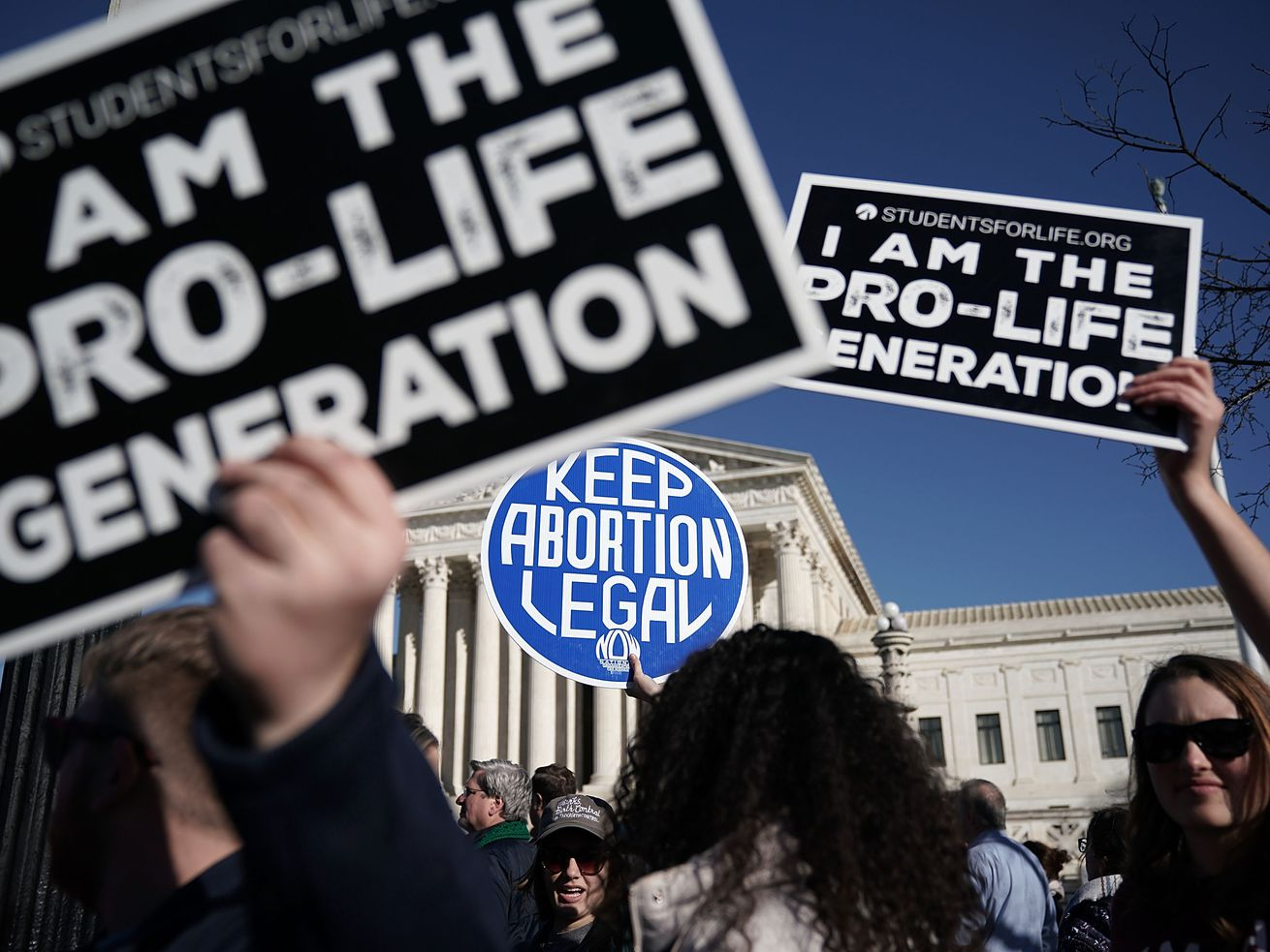 "Activists hold signs, some reading ""I am the pro-life generation,"" and one reading ""Keep aborton legal,"" outside the US Supreme Court."