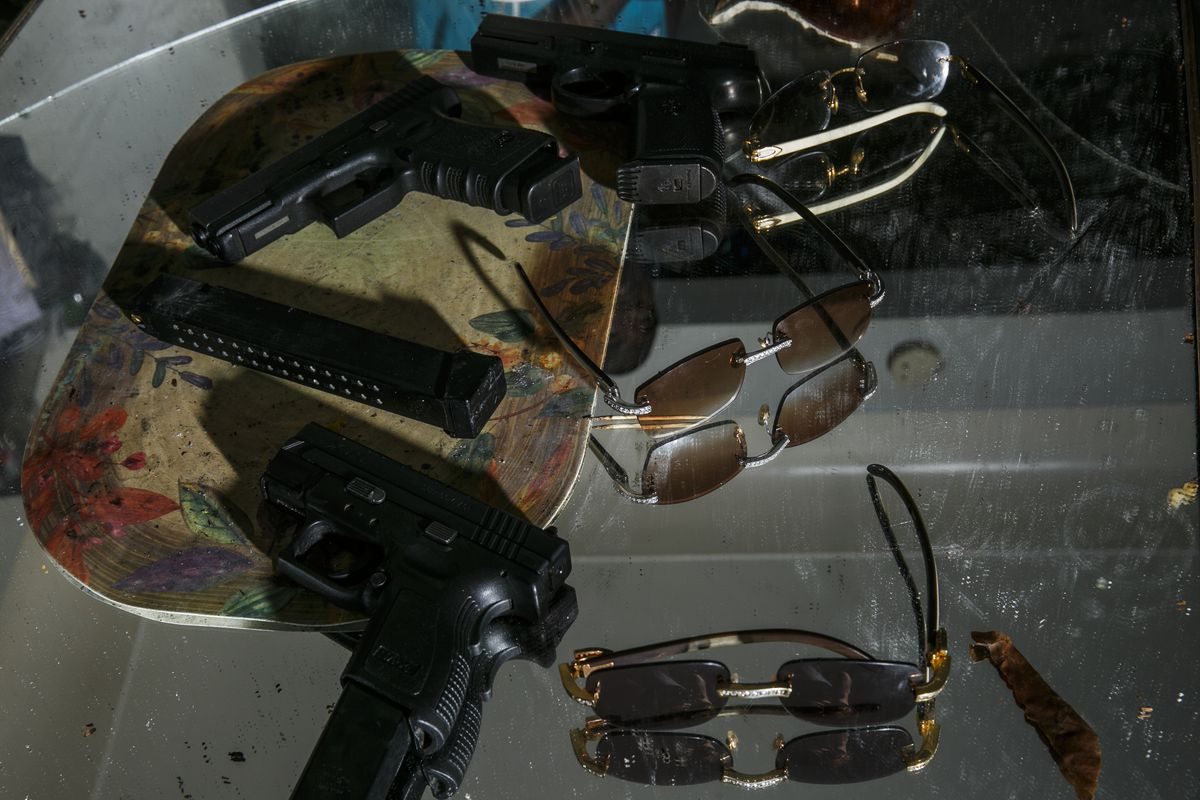 5a66ff8f17 Cartier glasses and handguns with extended clips lay on a table in a house  in Detroit