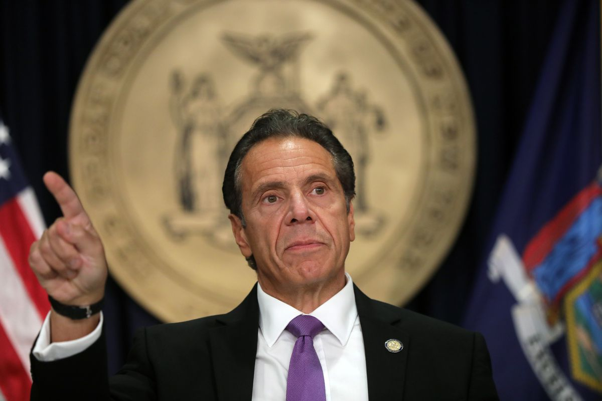 Gov. Cuomo, in a black suit, white shirt and purple tie, gestures in response to a question, standing in front of the state seal of New York.
