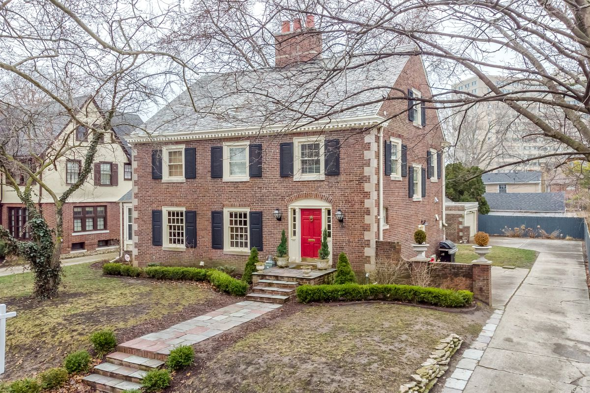 A stone walkway with a few steps leads to a two-story colonial with black window shutters and a read front door.