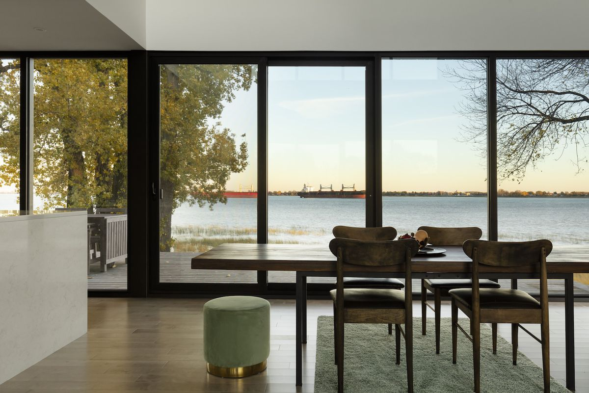 Dining room with large wooden table and views out to the river.
