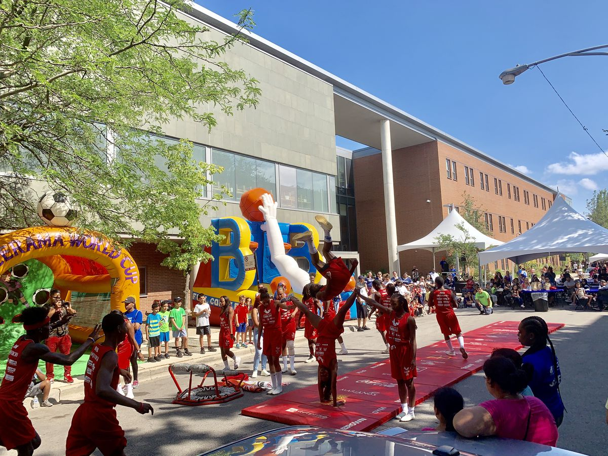 The Jesus White tumblers entertain students and parents in front of bouncy castles.