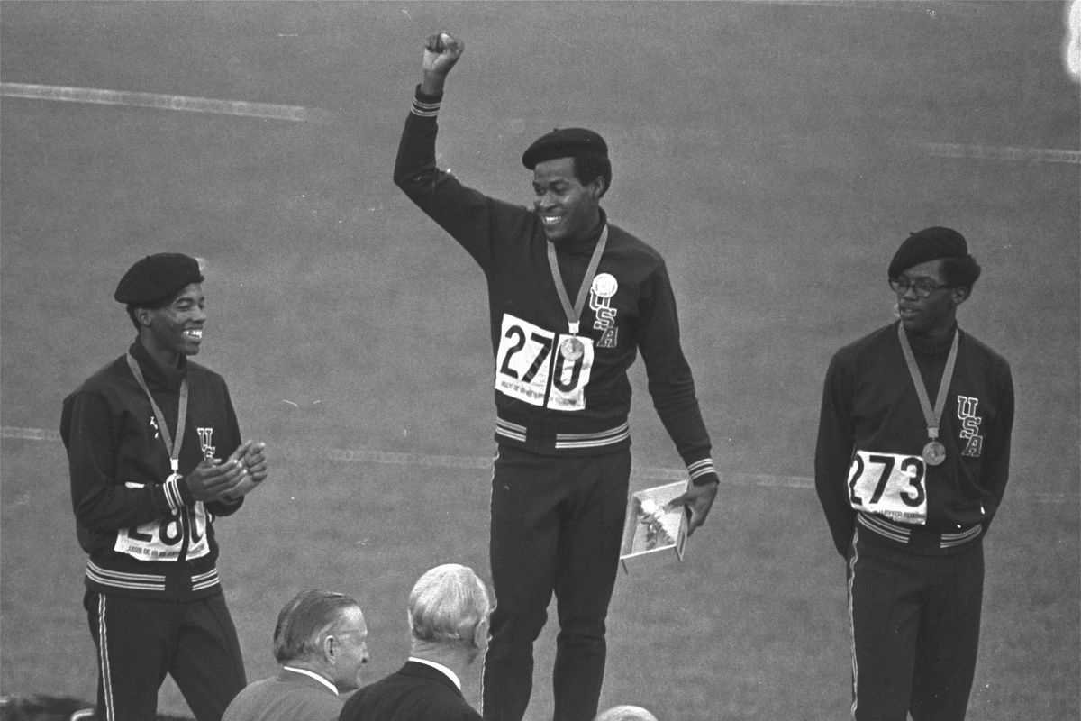 Lee Evans, center, the record-setting sprinter who wore a black beret in a sign of protest at the 1968 Olympics, died Wednesday. He was 74.