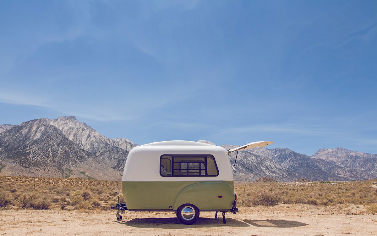 Small rounded camper trailer with large windows and open hatch-back set in a desert landscape.