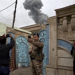 An Iraqi special forces lieutenant takes a selfie with the plume from an airstrike, during heavy fighting in the Yarmouk district of western Mosul, Iraq, Tuesday, April 11, 2017.