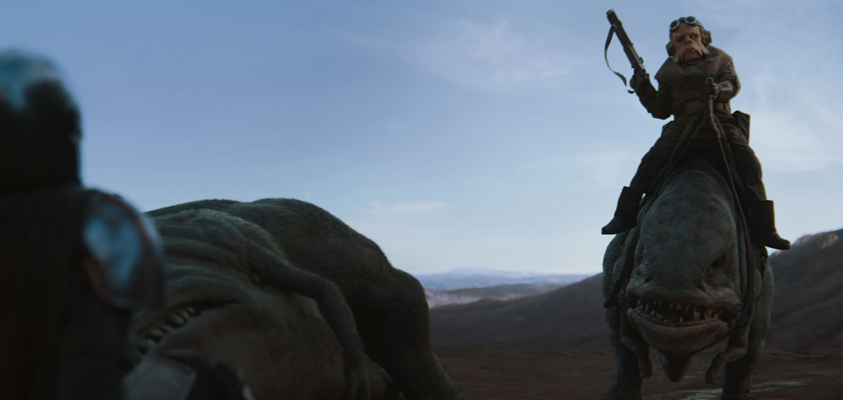 The Mandalorian is approached by a man on a pack animal.