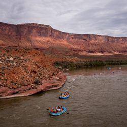 A raft carrying Sen. Mitt Romney, R-Utah, his wife, Ann, and Sen. Michael Bennet, D-Colo., second blue raft from the left, floats down a section of the Colorado River northeast of Moab on Saturday, Sept. 18, 2021.