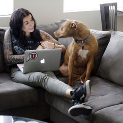 Kenzie Smith works on her computer with her boyfriend's dog, Harley, at her side in her apartment in Salt Lake City on Thursday, April 28, 2016.