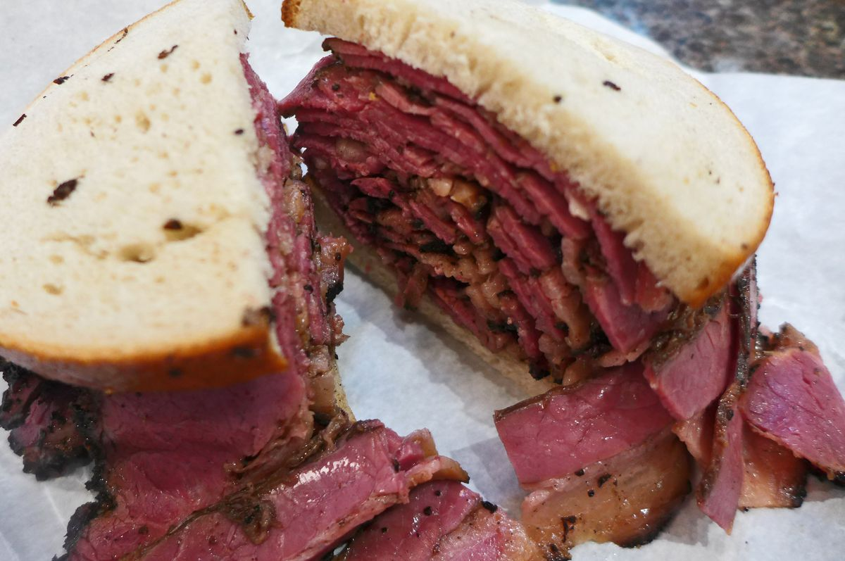 A thickly stacked pastrami on rye with a white wrapping paper underneath and very dark red pastrami sliced thin.