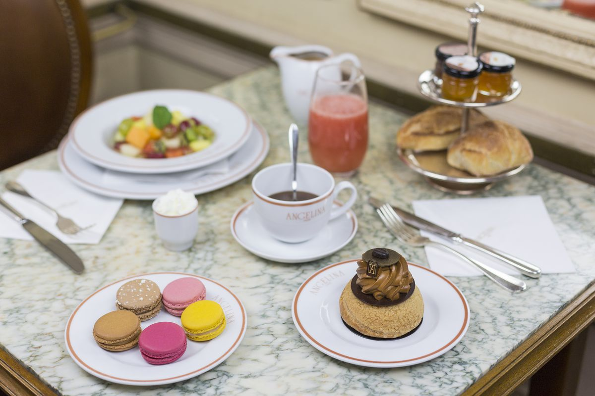 A cup of hot chocolate surrounded by small plates of pastries and cookies