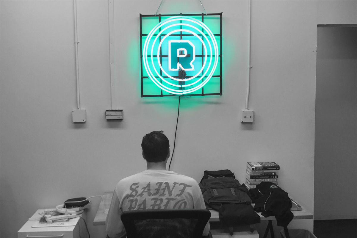 A man sitting in the Ringer office under a green Ringer logo