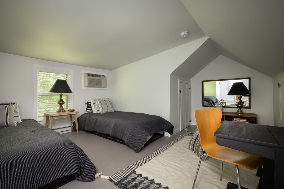 An upstairs loft has two twin beds and a small desk.
