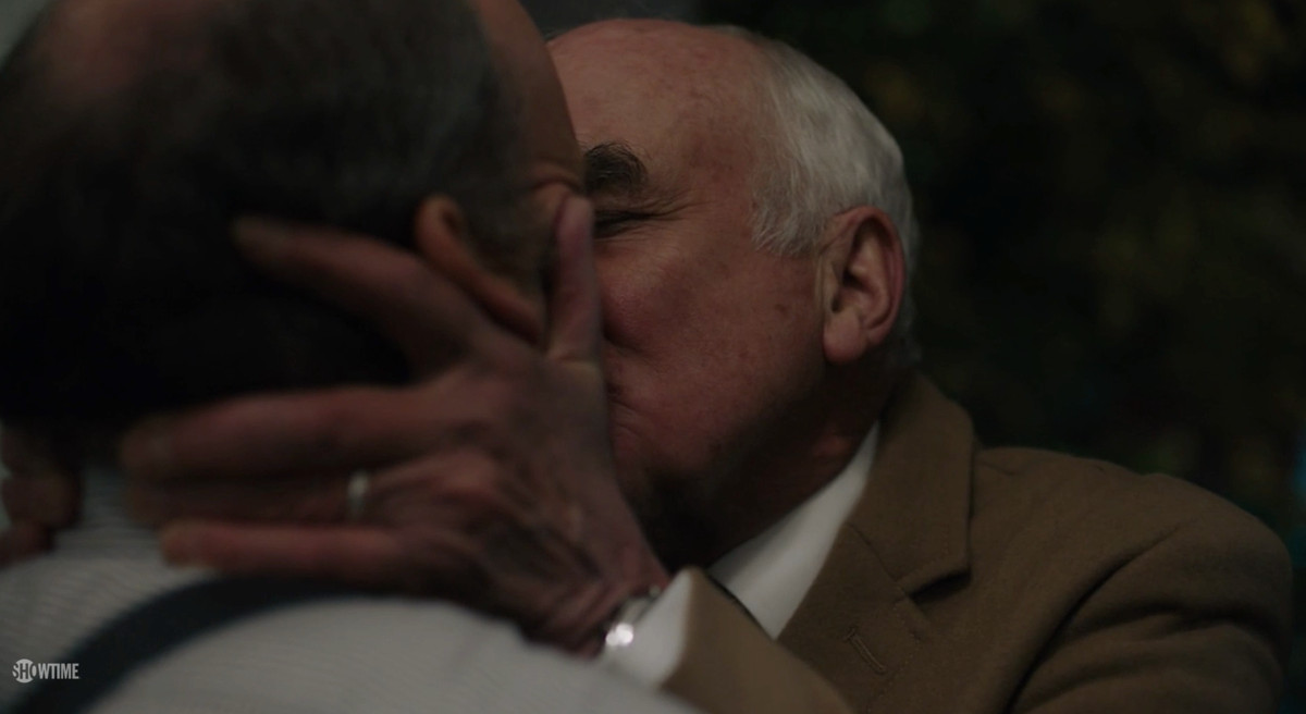 A close-up of Chuck Sr. twisting his son's ear while kissing him