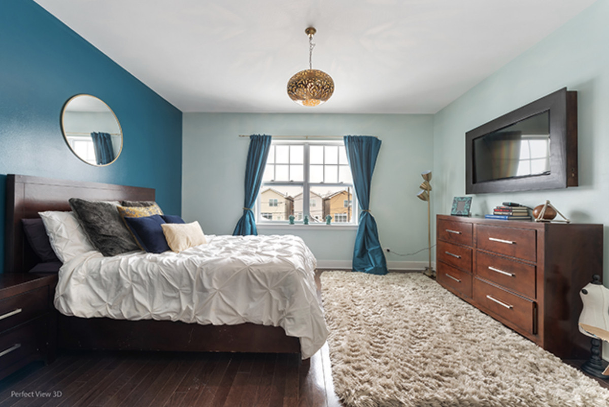 A bedroom with a dresser, window, gold light fixture, and a tv.