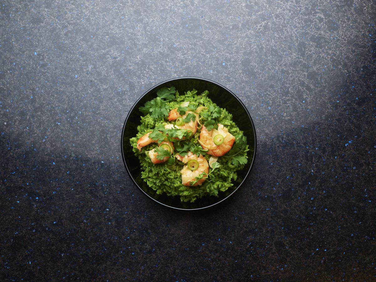 A plate of shrimp and green rice
