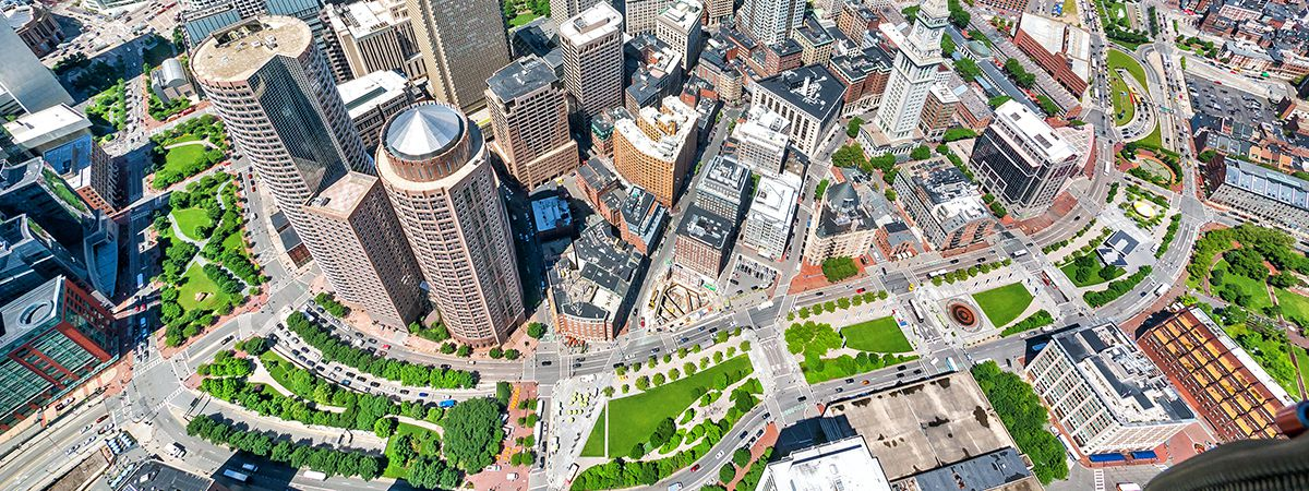 An aerial view shows the Rose Kennedy Greenway snaking through tall buildings of Downtown Boston