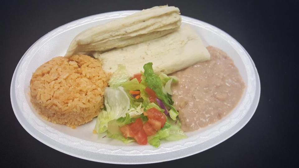 Plate containing rice, refried beans, tamale and burrito