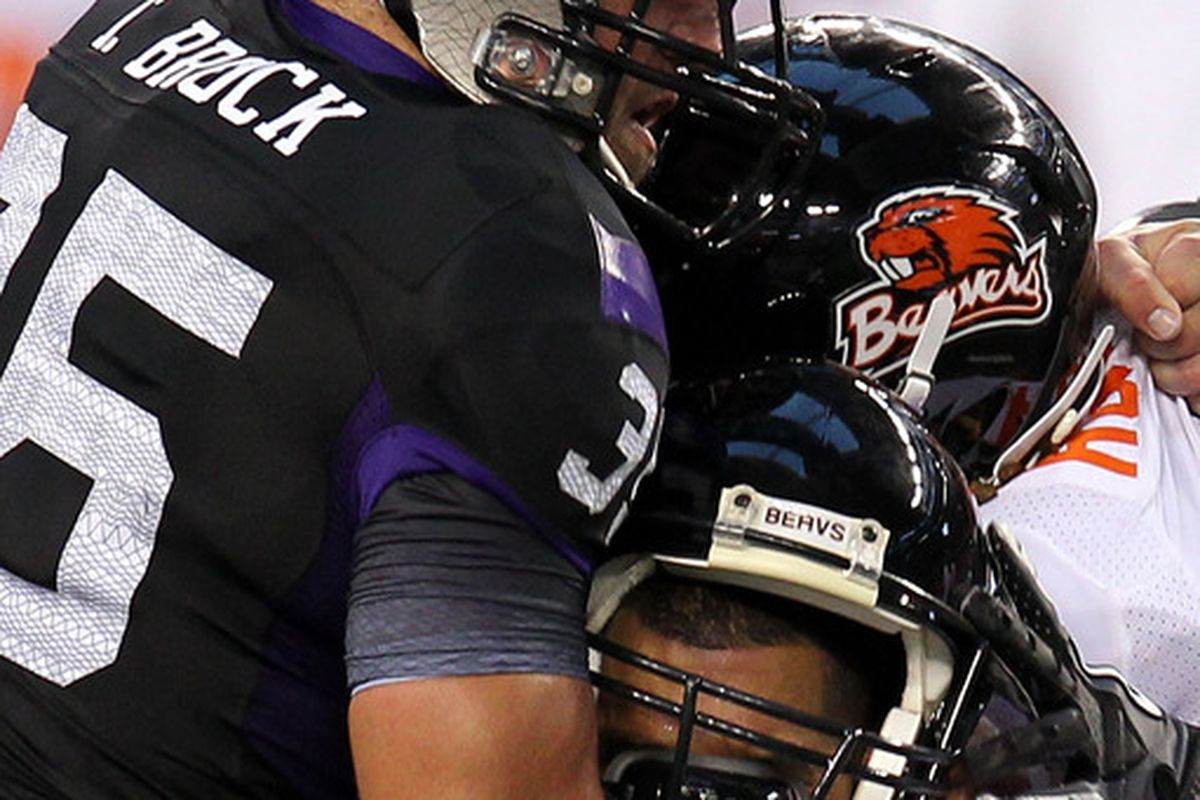 ARLINGTON TX - SEPTEMBER 04:  Quarterback Ryan Katz #12 of the Oregon State Beavers is tackled by Tanner Brock #35 of the TCU Horned Frogs at Cowboys Stadium on September 4 2010 in Arlington Texas.  (Photo by Ronald Martinez/Getty Images)