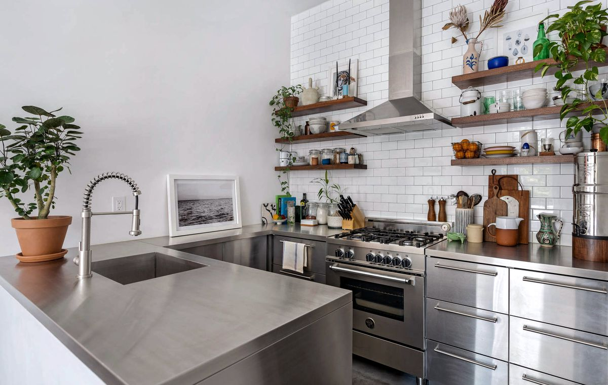 An open kitchen with a Bertazzoni range, white tile backsplash, and stainless-steel countertops.