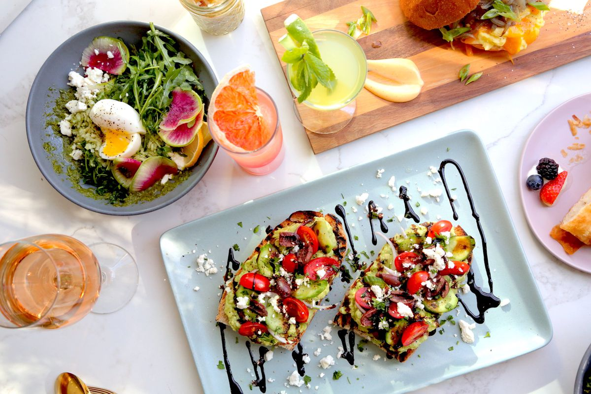 An overhead shot of sunny breakfast foods and a salad, with drink in the middle.