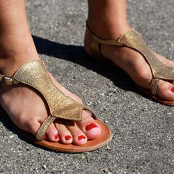 Golden flat sandals and cherry red toes, yes ma'am.