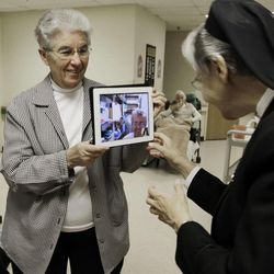 In this April 10, 2012, photo, sister Priscille Roy, left, holds up an iPad displaying her colleague, Sister Pauline Demers, who is in Brazil, to show Sister Elaine Lachance, right, at St. Joseph Convent in Biddeford, Maine. Good Shepherd Sisters of Quebec has just six convents in Maine and Massachusetts with fewer than 60 sisters. The youngest is 64, and it's been more than 20 years since a new member has joined. Sister Lachance is using the Internet, social media and even a blog to attract women who feel the calling to serve God.