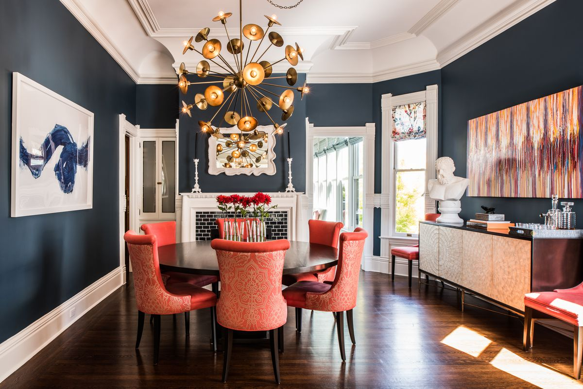 A Dark Blue Dining Room With Orange Accents