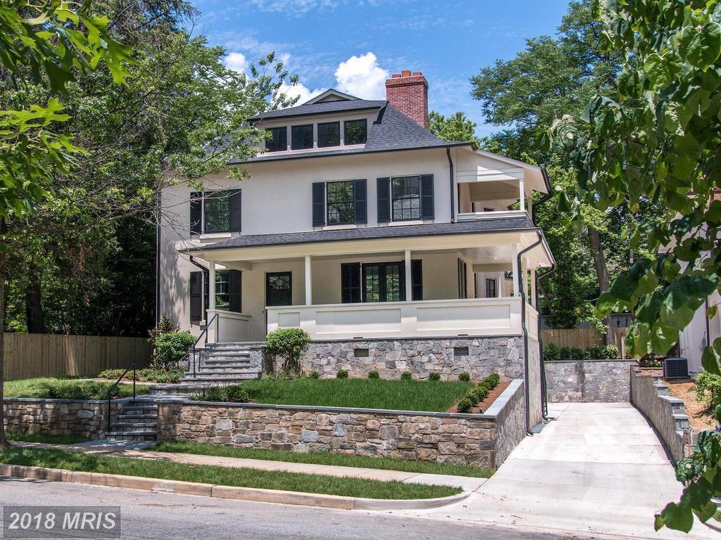 The exterior of a house in Washington D.C. The house has a yellow facade with a white porch.