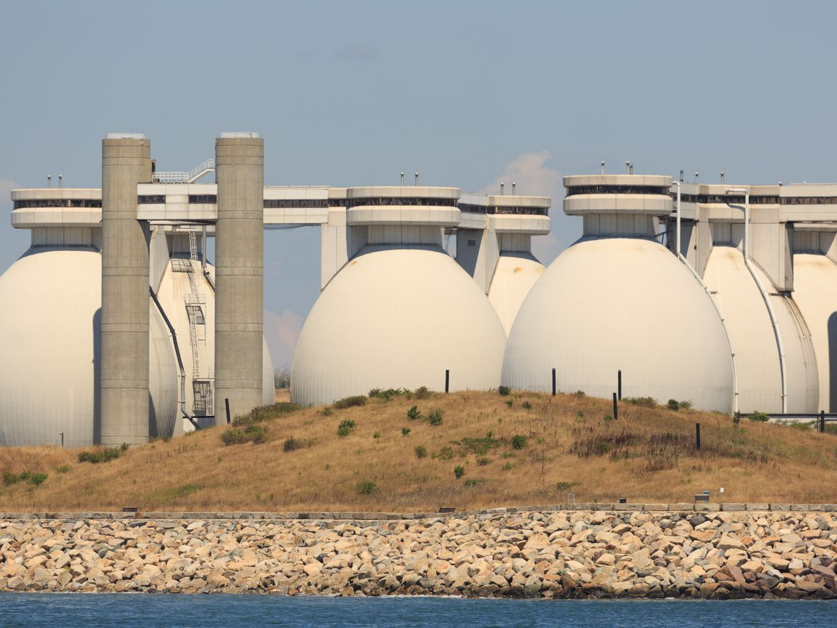The giant, cylindrical generators of a waste-treatment plant, with a barren landscape in front of them.