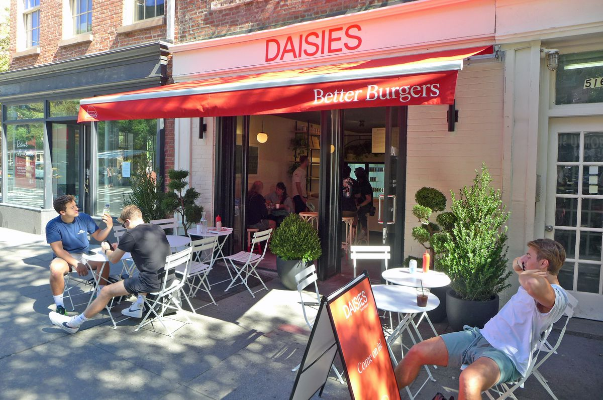 A sun-dappled sidewalk cafe with an open storefront and red awning, with a few dudes sitting around in front.